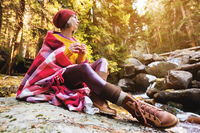 A pretty hipster girl with a plaid plaid on her shoulders in a hat and a yellow sweater and glasses with a mug of coffee in her hands looks at a mountain river sitting on a rock in a pine forest. The concept of freethinking travel around the world and the