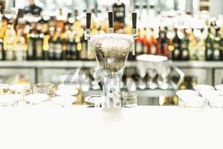 An der Bar - ein kühles Helles! Ein Zapfhahn mit kühlem Bier, im Hintergrund viele Getränkeflaschen.
