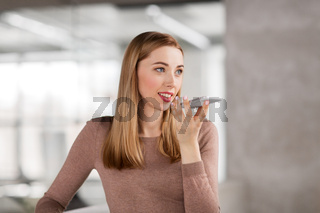 woman using voice recorder on smartphone at office