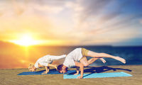 couple doing yoga side crane pose outdoors