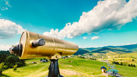 Golden tourist telescope and blurred mountains landscape in the background