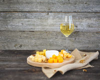 Set of different kind of cheeses with a glass of white wine