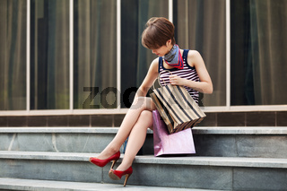 Young fashion woman with shopping bag sitting on the mall steps