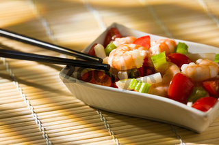 Shrimp salad inside a white bowl and chopsticks