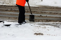 the worker cleans the railway tracks from the snow with a shovel in the place of automobile railway grade crossing