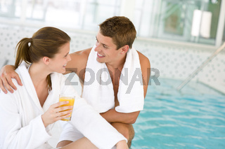 Young happy couple relax at swimming pool