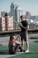 Sportive man and woman working out together on the roof.