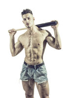 Sportive man posing with baseball bat
