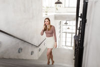 businesswoman with smartphone walking upstairs