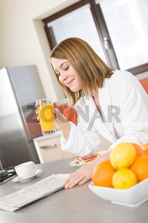 Breakfast - Smiling woman reading newspaper in kitchen