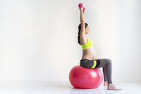 One young pregnant women doing fitness exercises