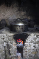 An old stone stove with an saucepan