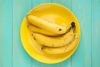 Yellow plate with healthy banana fruits