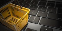 E-commerce, online shopping, internet purchases concept.  Yellow shopping basket on computer laptop keyboard,