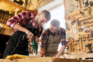 carpenters with drill drilling plank at workshop