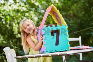 Mädchen baut aus Puzzleteilen ein Traumhaus