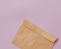 Brown craft envelope for mailing on pink background