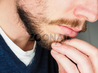 Male person, at closeup with fingers in beard