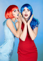 Portrait of young women in comic pop art make-up style. Shocked females in red and blue wigs
