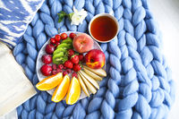 Plate with fresh fruit salad on a blue plaid with place for text