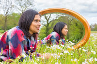 Woman lying in blooming meadow with mirror