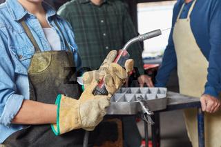 Arbeiter mit Handschuhen hält Schweißgerät