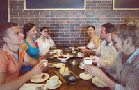 Six cheerful friends chatting while lunch in restaurant