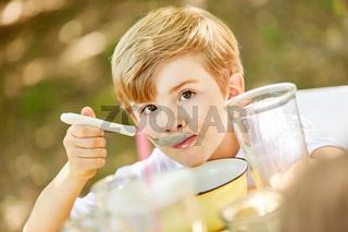 Junge isst gesundes Müsli morgens zum Frühstück