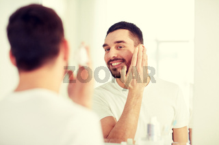 happy man applying shaving foam at bathroom mirror