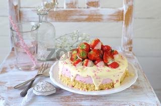 Erdbeer-Quark-Sahne-Torte mit weißem Schokoladenguss und rosa Zuckerperlen