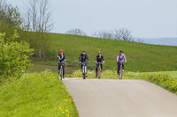 Four women riding a country road on a training trip