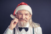 New year, old wrinkled man wearing Santa hat.