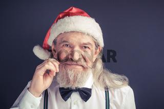 New year, old wrinkled man wearing Santa hat.