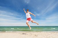 smiling young man jumping on summer beach