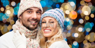 happy couple in hats over lights background