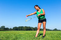 Woman serve with badminton racket and shuttle outside in grass
