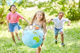 Fröhliches Mädchen läuft mit Weltkugel