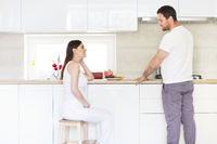 Pregnant woman and happy man in the kitchen
