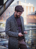 Handsome trendy man typing on cell phone