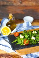 Fresh italian caprese salad with mozzarella and tomatoes on dark plate