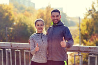 smiling couple showing thumbs up outdoors