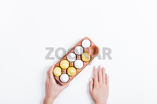 Woman's hands holding a tray with yellow Easter eggs on white background
