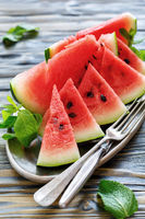 Slices of sweet watermelon, fork and knife on the tray.