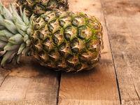 Organic pineapples on rustic wood