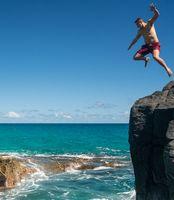 Fit young man jumps into ocean at Lumahai beach Kauai