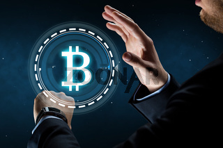 businessman with smart watch and bitcoin hologram