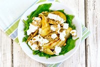 Salad from pear and spinach in dish on light board top