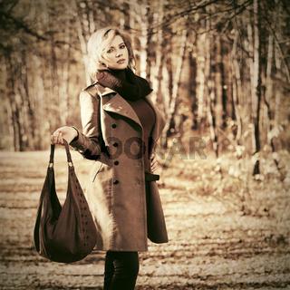Happy blond fashion woman with handbag walking outdoor