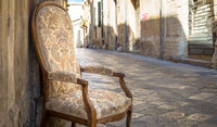 Old chair in a traditional street of Lecce, Italy.