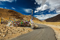 Road and Buddhist prayer flags (lungta) at Namshang La pass. Lad